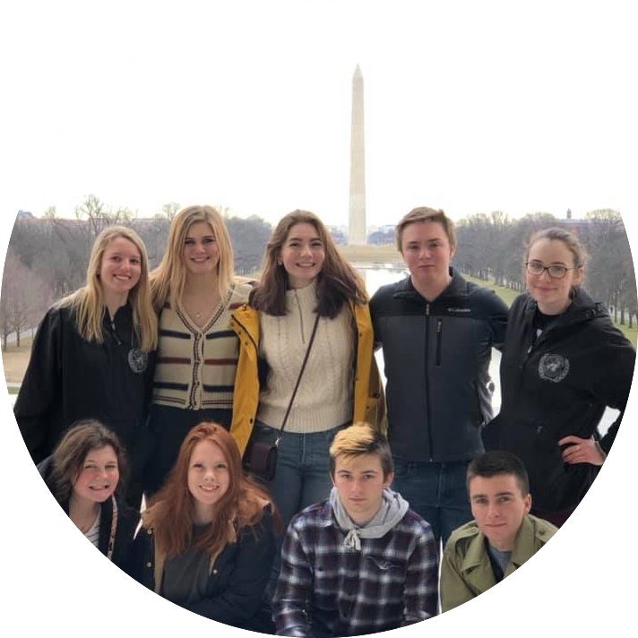 Nine Model UN students standing on the Lincoln Memorial steps with the Washington Monument in the background.