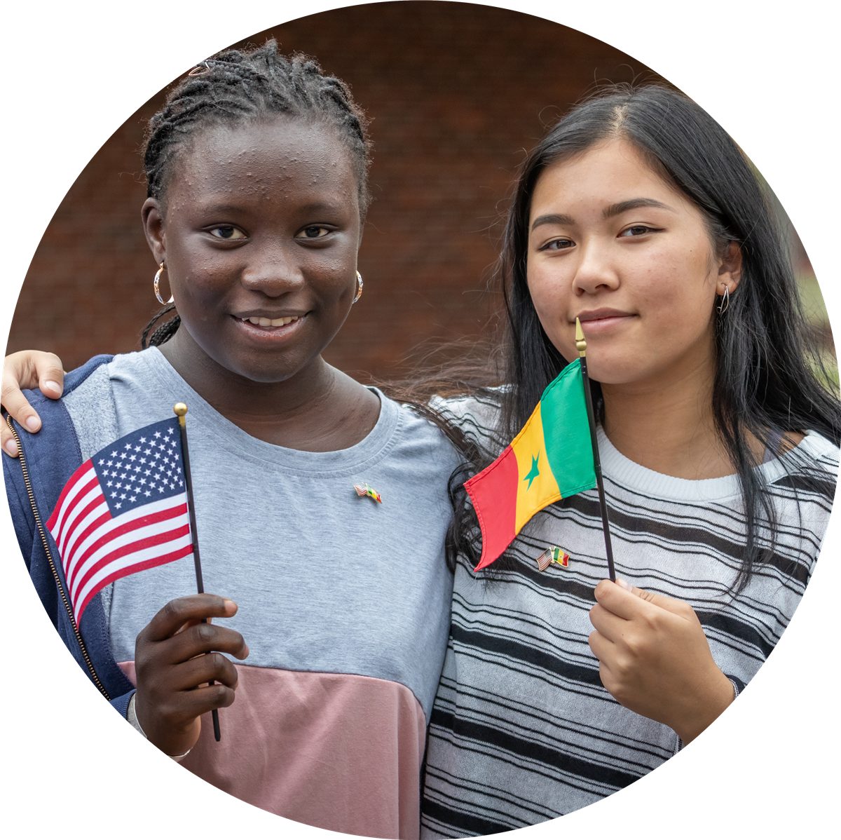 Two girls from Woodstock Academy and Senegal hold American and Senegalese flags.