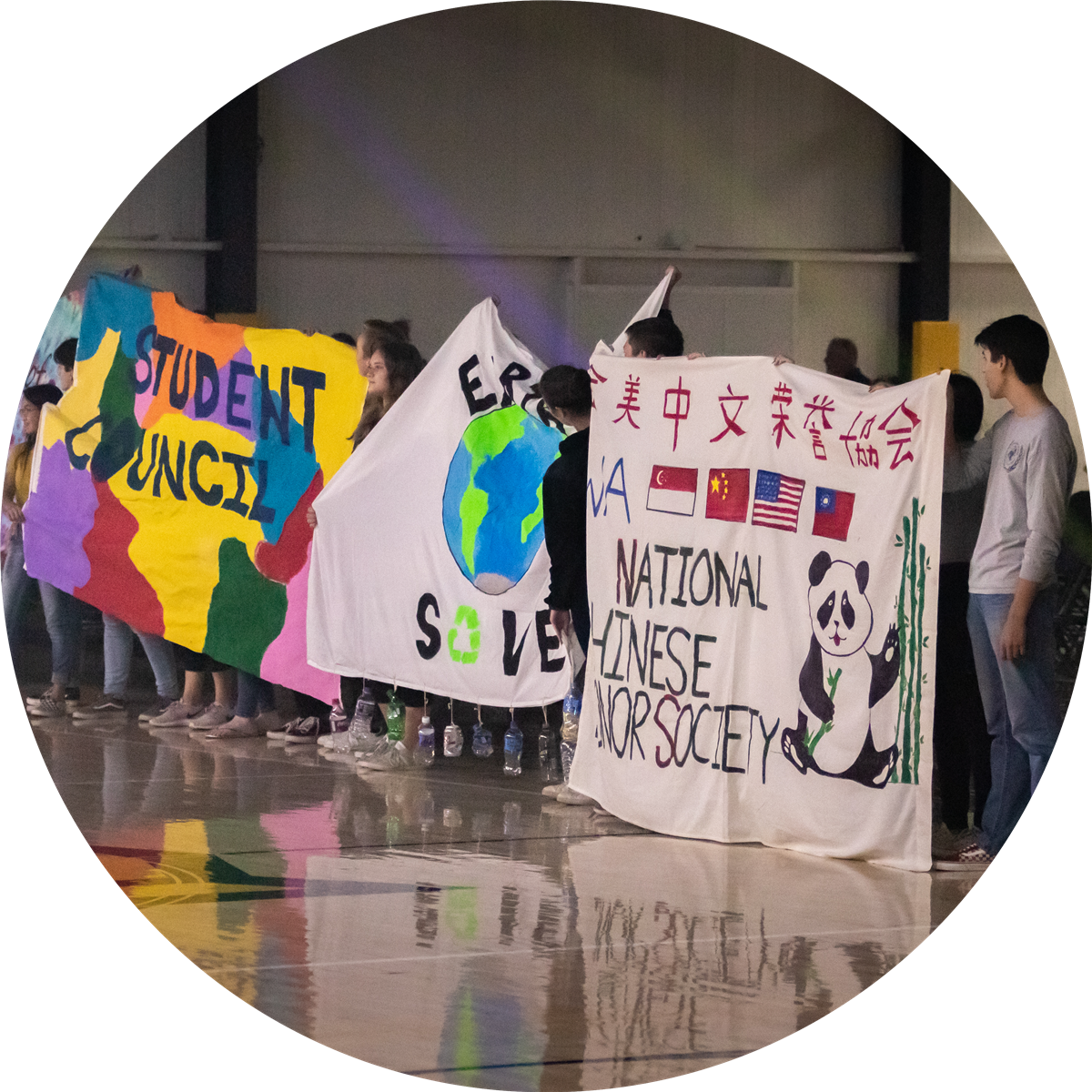 Students with painted banners for student council, earthsave, and national chinese honor society